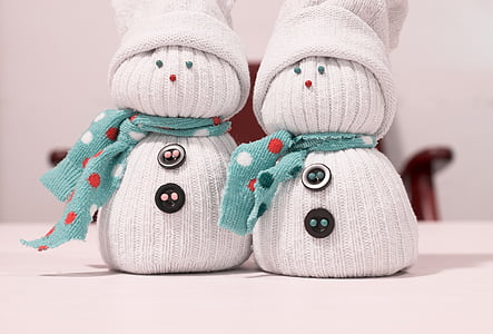 two white-and-teal snowman sock dolls