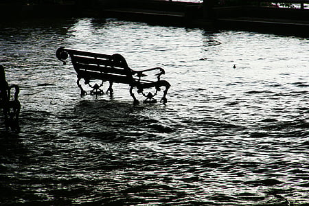 black metal park bench at the middle of body of water
