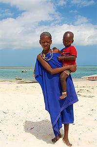 woman carrying a baby near seashore
