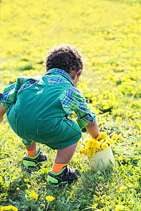 boy holding white bucket with yellow petaled flower bouquet