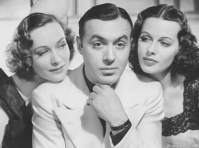 grayscale photo of man in suit jacket between two women