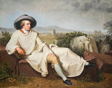 man wearing white top sitting on brown concrete brick painting