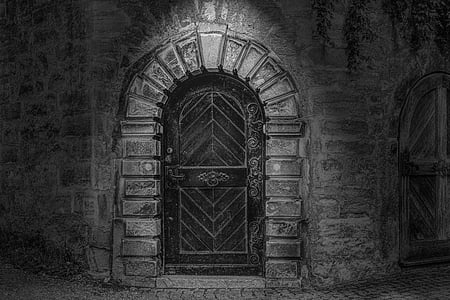 grayscale photo of arch-shaped black wooden panel door