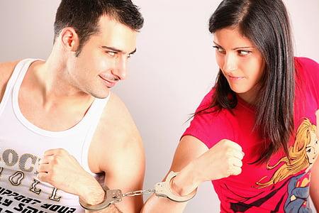 man and woman wearing handcuffs