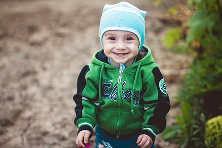 boy in green and black full-zip hoodie wearing blue and white knit cap