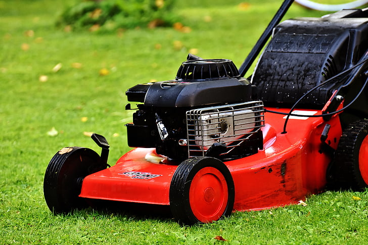 photo of black and red push lawn mower on grass field