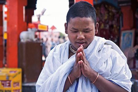 man wearing white scarf while praying during daytime