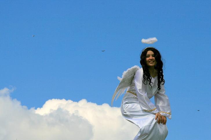 angel sitting on cloud under clear sky