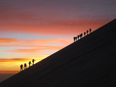 silhouette photo of hikers with background of sunset