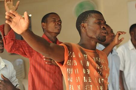 man wearing orange crew-neck shirt raising right hand