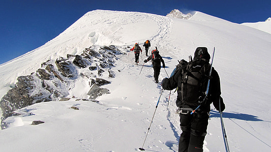 group of people climbing on mountain coated by snow
