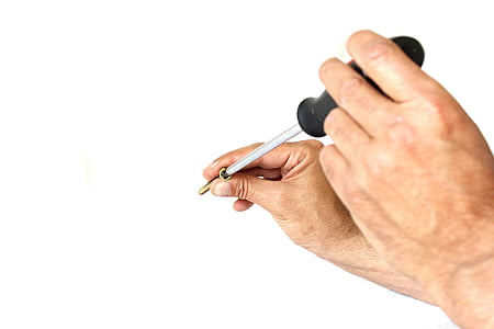 person holding screw and screwdriver