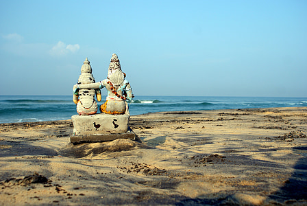 two deity statuette on seashore at daytime