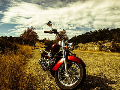 red and black touring motorcycle near grass under cloudy sky at daytime