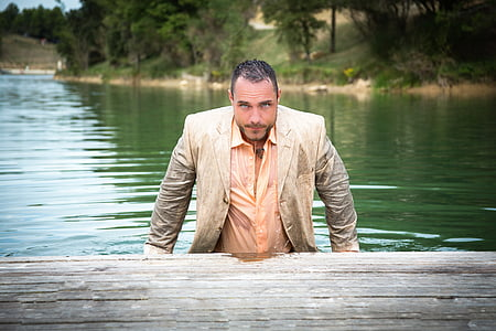 man in beige notched lapel suit on body of water