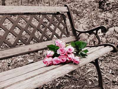 red rose arrangement on brown wooden bench