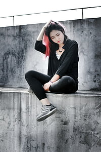 woman wearing black hoodie and touching her hair