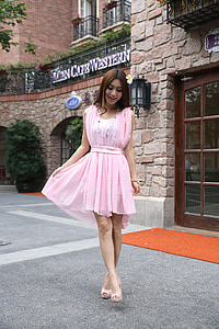 woman wearing pink mini dress outside coffee shop