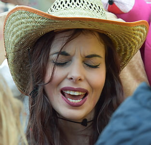 woman in brown sunhat surrounded by people