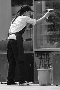 grayscale photography of woman cleaning window