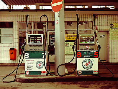 white post in between two assorted-color gasoline pumps dispensers near tiled wall