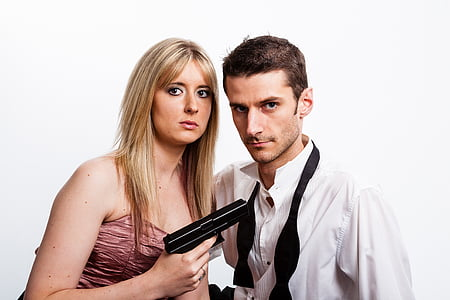woman holding pistol while pointing at man beside