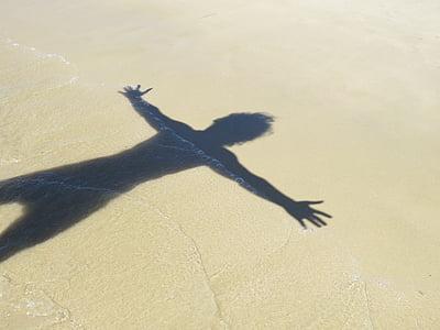 human shadow on beach sand during daytime