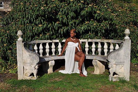 photo of woman wearing white dress sitting on concrete bench