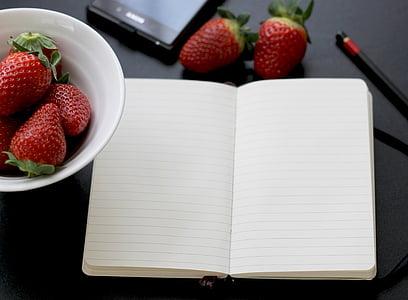 white notebook near strawberries