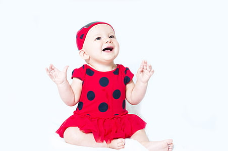 baby in red and black polka-dot shirt dress