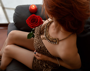woman in brown and beige leopard pattern straight across dress holding red rose
