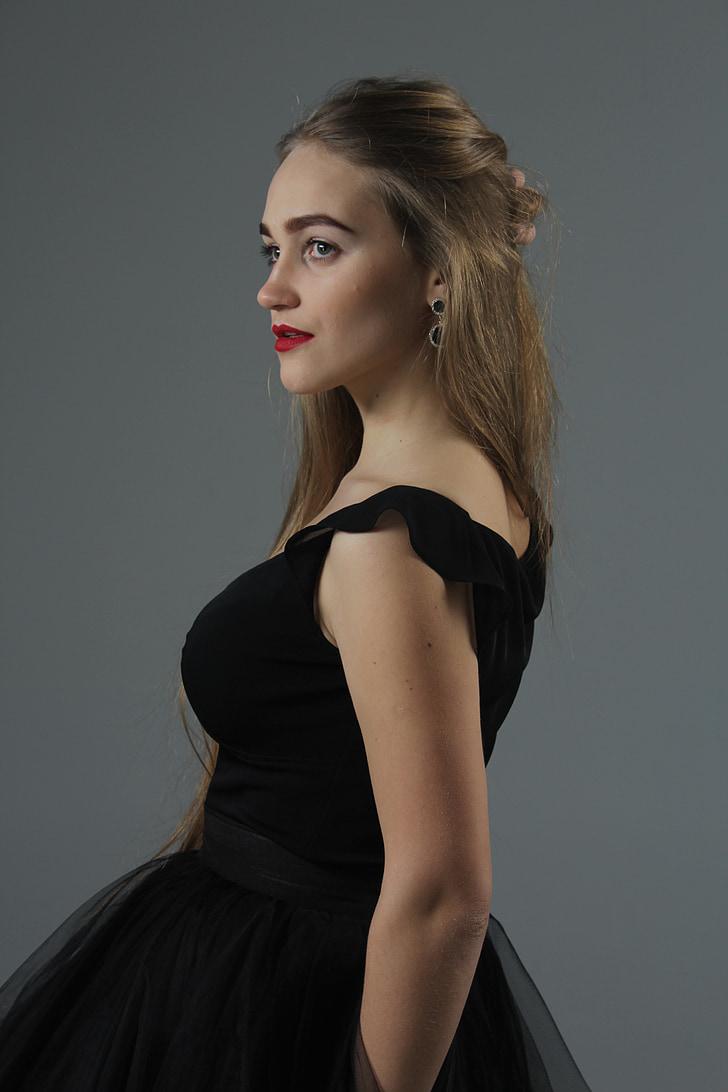 woman wears black sleeveless dress