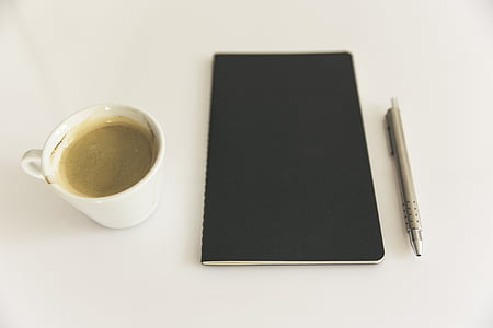 black notebook beside mug and pen