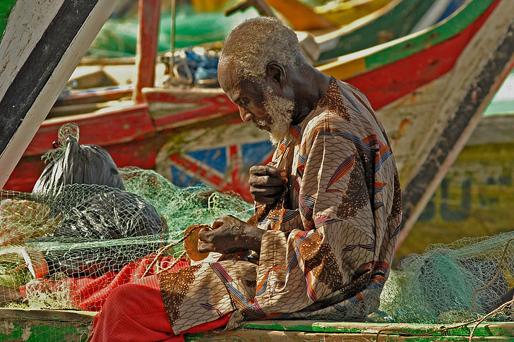 fisher man knitting the net on the boat