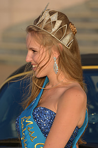 brown haired woman in blue dress with gold-colored tiara