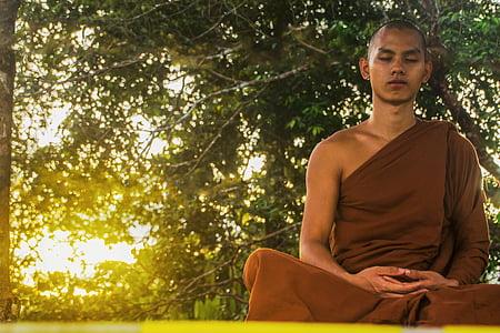 photo of man in brown kasaya robe meditating