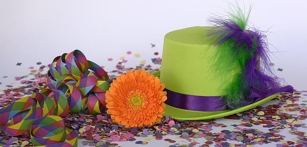 green and purple hat beside orange flower on top of confetti