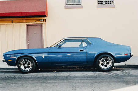 classic blue Ford Mustang coupe parked beside white building