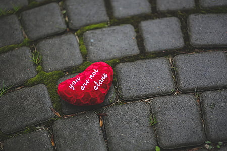 photo of red heart with text on gray pavement