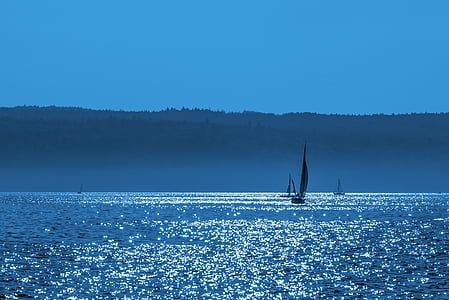 silhouette of sailboat under blue sky