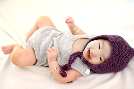 baby wearing purple aviator hat