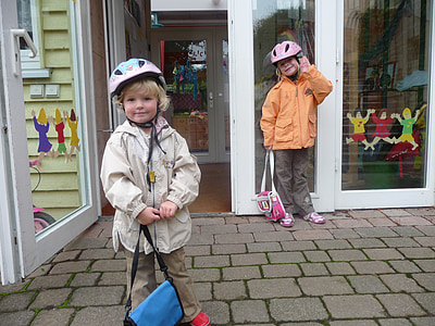 two children's wearing jackets and bicycle helmets