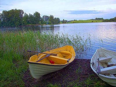 canoe beside green grass near body of water
