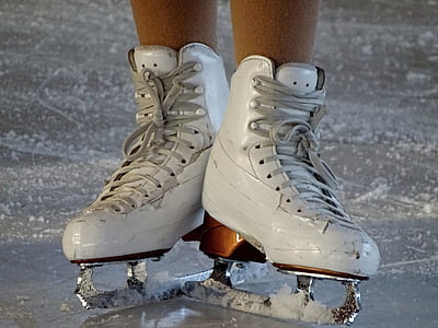 person wearing white figure skates