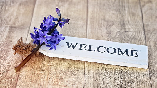 white wooden Welcome signage on brown wooden surface