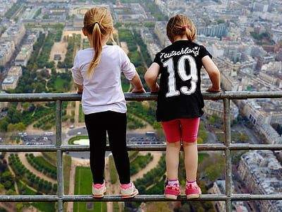 girl wearing black and white 19 jersey shirt beside girl wearing white shirt on gray metal rail at daytime