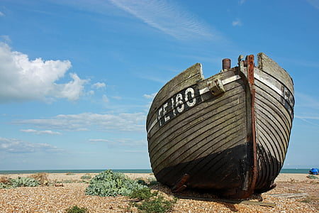 brown boat on seashore near body of water