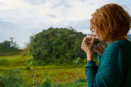 woman sipping drink from mug with trees in background