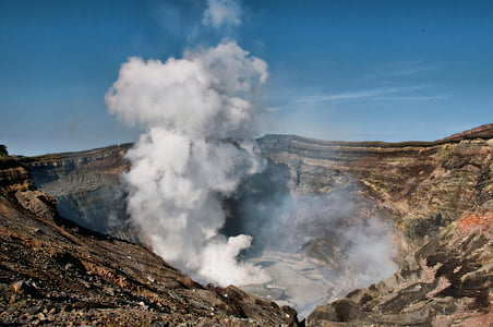 volcanic crater spews white smoke