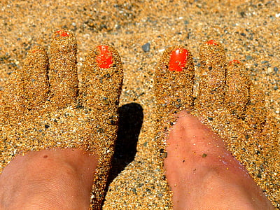 human feet covered with sand